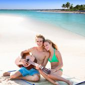 stock photo of couple sitting beach  - Blond young tourist couple playing guitar at beach in Mexico Caribbean photo mount - JPG