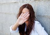 foto of shy girl  - Shy brunette girl covering her face with a grey wall of background - JPG