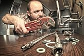 stock photo of plumber  - plumber at work indoor shot - JPG