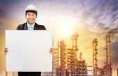 picture of broad-bodied  - engineering man with white empty white broad standing in front of oil refinery industry estate use for industrial theme - JPG