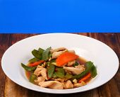 image of stir fry  - chicken stir fry thai style on a blue background on a wood table - JPG