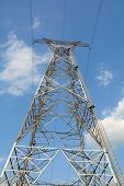stock photo of power transmission lines  - Electric power lines and pylon against blue sky - JPG