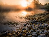 foto of swamps  - Stones before the water of a swamp with the rising sun in the background - JPG