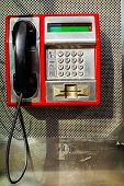 picture of dial pad  - Red public telephone is attached on metallic background phone and headset - JPG
