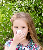 foto of allergies  - Little girl has allergy to spring blossoming and blowing her nose outdoor - JPG