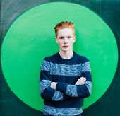 stock photo of redhead  - Young redhead man in a sweater and jeans standing next to green wall with folded arms - JPG