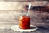 pic of jar jelly  - Jar of tasty jam on wooden background - JPG