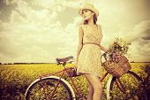 picture of romantic  - Romantic young woman stands in a field with her bicycle and a basket with wild flowers - JPG