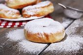 image of icing  - Delicious donuts with icing and powdered sugar on wooden background - JPG