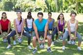picture of kettles  - Fitness group squatting in park with kettle bells on a sunny day - JPG