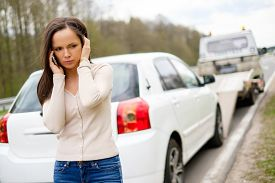 stock photo of trucks  - Woman calling while tow truck picking up her car - JPG