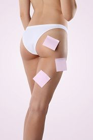 image of bum  - Bum and legs of slim woman over pink background with post it - JPG