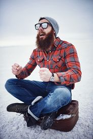 stock photo of hobo  - hyped up hobo like hipster with manly awesome beard and sunglasses sitting on retro suicase in empty desolate salt flats - JPG