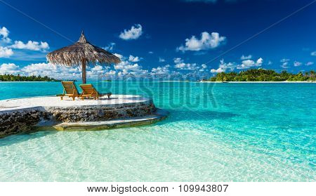 Two chairs and umbrella on a jetty on a tropical island, Maldives