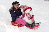 image of toboggan  - Girl with toboggan and snowman fun with snow at wintertime - JPG