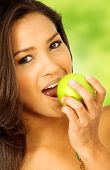 image of pretty girl  - beautiful latin american girl eating an apple outdoors - JPG