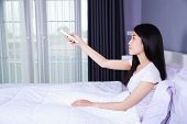 woman hand hold remote air conditioner on bed in the bedroom