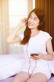 woman in headphones listening to music from smartphone on bed in the bedroom