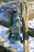 stock photo of lamp post  - an old oil lamp hanging from a wood fence post - JPG