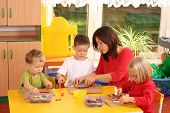 picture of 6 year old  - teacher and three preschoolers playing with wooden blocks - JPG