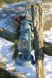 foto of lamp post  - an old oil lamp hanging from a wood fence post - JPG