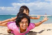 stock photo of babysitting  - asian ethnic mother and child happy playing at the tropical beach - JPG