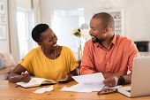 Mature couple sitting and managing expenses at home. Happy african man and woman paying bills and ma poster