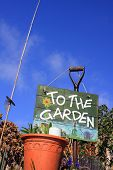 picture of frot  - A portrait format image set at a low angle of a terracotta coloured flower pot set in frot of a garden fork with a hand painted sign with garden themed images and text spelling  - JPG