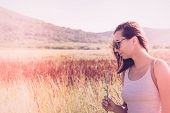 Traveler Girl Relaxing In Fields. Young Girl Traveler Relaxing In Nature. Traveler With Flower In Na poster