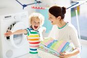 Family In Laundry Room With Washing Machine poster