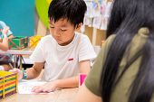 Kids Are Painting Picture With Color Pencil With Their Teacher In The Classroom To Learn Paint Skill poster