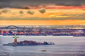 New York Harbor, New York, USA with the statue of liberty and Bayonne, New Jersey in the background. poster