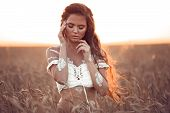 Boho Chic Style. Portrait Of Bohemian Girl With White Art Posing Over Wheat Field Enjoying At Sunset poster