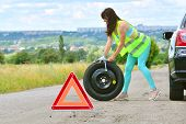 Girl Has A Problem With Spare Wheel Replacement. Punched Wheel On The Road While Driving. Girl L In  poster