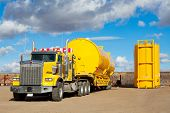 stock photo of tractor trailer  - A yellow transport trailer picking up two newly manufactured and coated 400 BBL - JPG