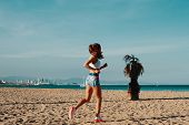 Nice Day For Jogging. Full Length Of Beautiful Young Woman In Sports Clothing Jogging While Exercisi poster