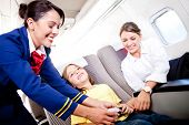 stock photo of cabin crew  - Flight attendant fastening seat belt to boy for a safe trip - JPG