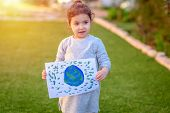 Portrait Of The Cute Little Girl Holding The Drawing Earth Globe Outdoor Sunny Day. Child Drawing A  poster