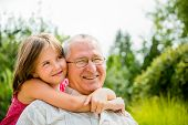 stock photo of granddaughter  - Outdoor lifestyle portrait of grandchild embracing grandfather - JPG