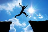 stock photo of cliffs  - Man jump through the gap - JPG