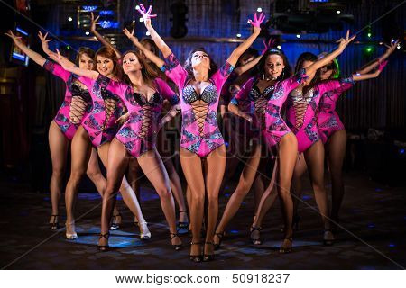 poster of Nine beautiful showgirls in purple costumes with raised hands perform on stage