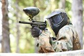 stock photo of paintball  - paintball player in protective uniform and mask aiming gun before shooting in summer - JPG