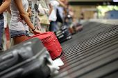 foto of commutator  - Suitcase on luggage conveyor belt in the baggage claim at airport - JPG