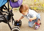 A Child Playing With A Baby Carriage.