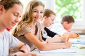 stock photo of exams  - Students or pupils of school class writing an exam test in classroom concentrating on their work - JPG