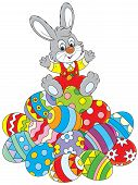 picture of cony  - Little rabbit sitting on a pile of colorfully painted Easter eggs - JPG