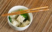 foto of chopsticks  - Close up horizontal top view photo of freshly made wonton with chopsticks on top of white bowl