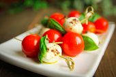 Bocconcini with basil and cherry tomatoes on skewer