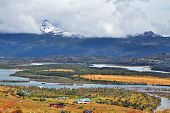 Patagonia. The picturesque valley is crossed by a winding river. On the horizon - snow-capped mounta