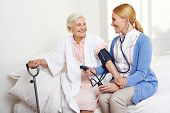 Geriatric nurse measuring blood pressure of senior citizen woman in nursing home